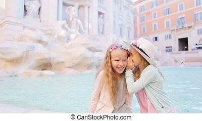 Adorable little girls whispering sitting on the edge of...