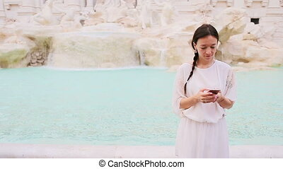 Young woman with smart phone near famous Fontana di Trevi -...