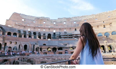 Young female tourist looking at the Colosseum inside in...