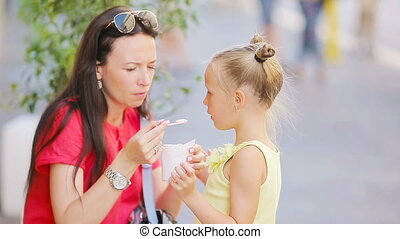 Young mother and her daughters eating ice cream outdoors. Mum feeds his daughter ice-cream in the street