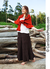 Young woman on logs in the forest - Young pretty woman...