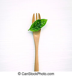 Closeup fresh sweet basil leaves with fork on white wooden...