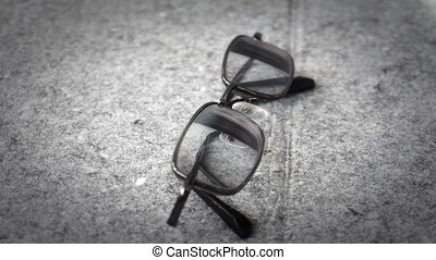 Men's glasses with a thin rim on a gray background closeup....