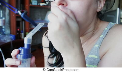 Girl is Breathing a Steam Through an Inhaler patiently -...