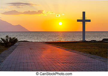 Silhouette of cross at sunrise or sunset with light rays and...