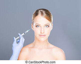 Doctor injecting botox into face of a young woman