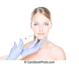 Doctor injecting botox into face of a young woman - Doctor...