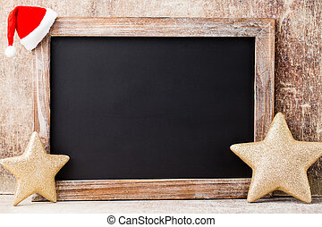 Christmas chalkboard and decoration over wooden background