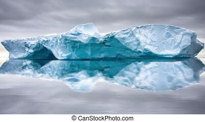 Big glacier in the snow with reslection in water. Slow...