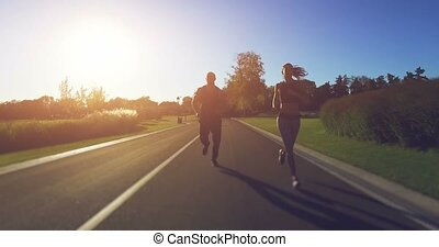 Couple jogging in the park. 4k, 25 fps - 4K shooting: Young...