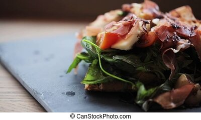 prosciutto ham salad on stone plate at restaurant - food,...