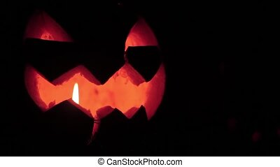 Closeup of scary holiday halloween carved glowing pumpkins....
