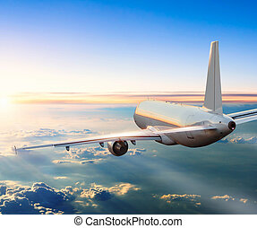 Airplane flying above clouds in dramatic sunset - Commercial...