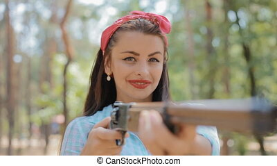 Pin up woman hold gun in her hands - Caucasian woman pose to...