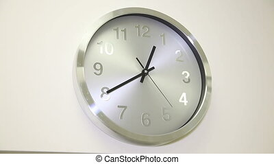 The clock on the white wall - The round clock on the wall in...