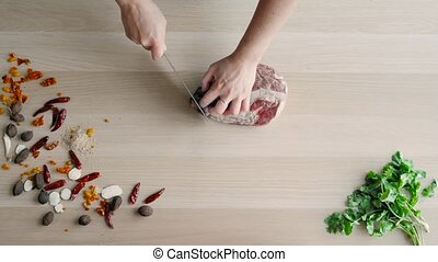 Top View of Chefs Hands Cutting Beaf. Raw Meat Slices...