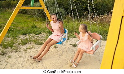 Mom and daughter on a swing - Mom and daughter ride on a...