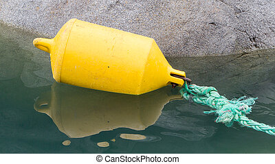 Inflatable yellow fender attached to a green rope