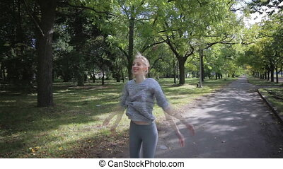 Young and beautiful girl doing exercise with jumps and...