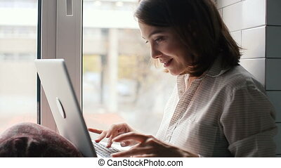 Girl typing on a laptop sitting on window - Girl typing on a...