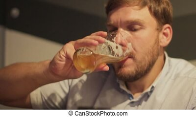man drinking beer in a bar alone
