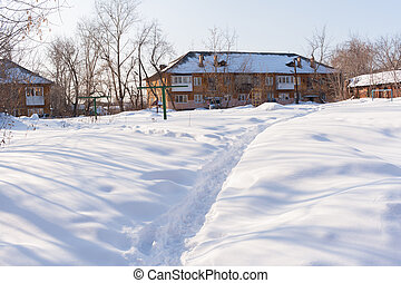A narrow path in the white snow, leading to the two-story...