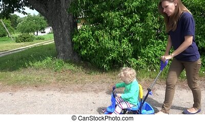 Young woman mother pushing blond toddler girl on small tricycle.