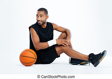 Happy young man basketball player sitting and looking away...