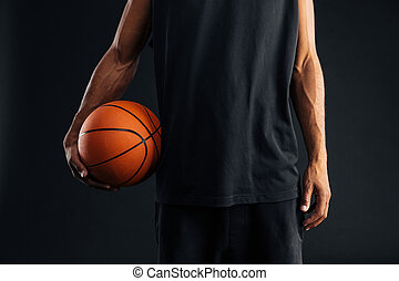 Cropped image of an african basketball player holding ball...