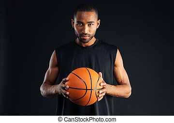 Portrait of a serious confident basketball player isolated...