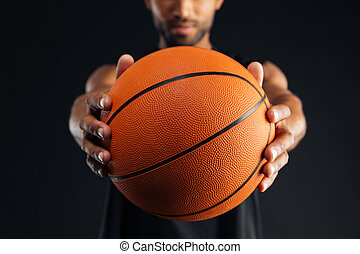 Cropped image of a focused african basketball player giving...