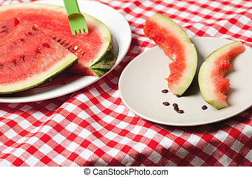 the watermelon on picnic tablecloth - photo shot of the...
