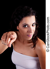 beautiful woman pointing, isolated on black background. Studio shot.