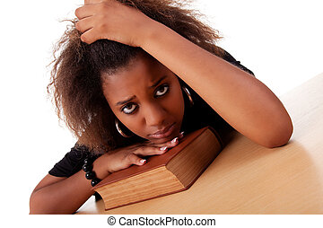 woman stressed ,with her head resting upon the book,...