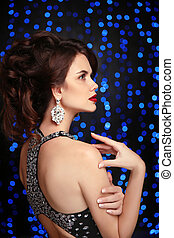 Elegant lady with red lips, hairstyle, diamond earrings posing isolated on studio dark blue party lights background.