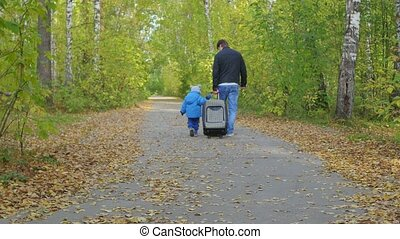 Man and child with a suitcase walking on a forest path in...