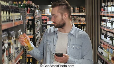 Man chooses beverages at the supermarket - Young man...