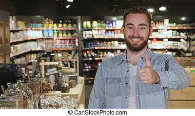 Man shows his thumb up at the mall - Caucasian bearded man...