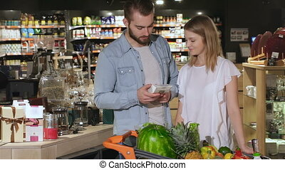 Couple choose tea at the hypermarket - Young couple choosing...