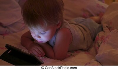 A little boy watches cartoons in the smartphone late in the evening