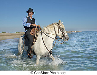 horse rider in the sea - horseman and his Camargue horse in...