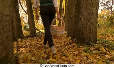 Slender brunette girl walking through autumn forest holding...