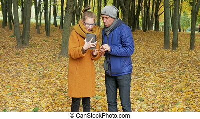 Daughter teenager teaches his father to work with the tablet in the autumn park. Dad listens carefully and repeats the daughter of her touch display