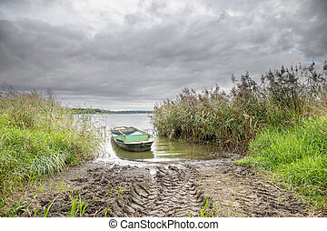 Small boat on the pond with reed under dramatic sky - Small...
