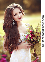 Wedding Portrait Of Beautiful Happy Bride with long wavy hair holding bouquet