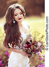 Wedding Portrait Of Beautiful brunette bride with long wavy hair holding bouquet of rose flowers posing in autumn park.