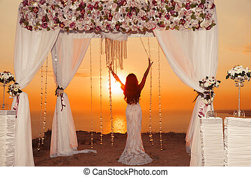 Sunset. bride silhouette. Wedding ceremony arch with flower arrangement and white curtain on cliff above sea, outdoor photo.