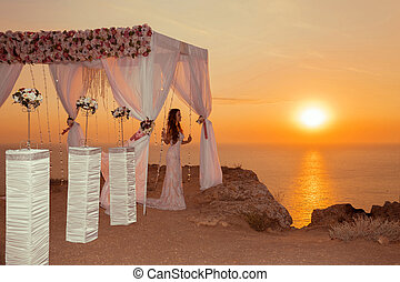 Wedding ceremony arch with flower arrangement and white...