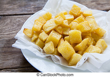 Fried potatoes - portions of fried potatoes on white paper...