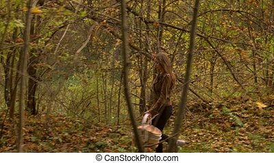 Beautiful slender girl walking in autumn forest holding a picnic basket. Profile view 4K steadicam video